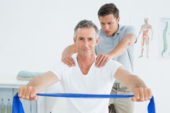 Therapist massaging mans shoulder in hospital Stock Photo