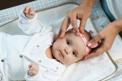 Therapist measures  size head of  beautiful baby Stock Image