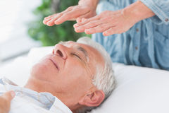 Therapist performing Reiki over senior man stock image