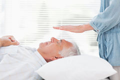 Therapist performing Reiki over senior man Stock Photo