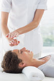 Therapist performing Reiki over woman Stock Images