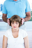 Therapist performing reiki over woman. Therapist performing reiki over women at health center Royalty Free Stock Image