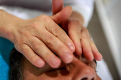 A therapist places his hands over the head of his patient Royalty Free Stock Photos