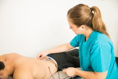 Free Therapist Positioning Electrodes On Customer For Lower Back Muscle Treatment Royalty Free Stock Photos - 124485688
