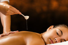 Therapist pouring Ayurvedic oil on female back. Stock Photos