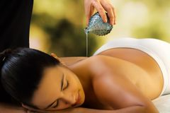 Therapist pouring massage oil on woman`s back. royalty free stock image