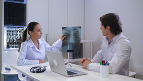 Therapist and pulmonologist in sitting in office. Two doctors in the hospital looking on x-ray of the lungs. Mixed race woman doctor discussing with caucasian stock video footage