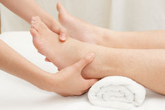 Therapist's hands massaging female foot Stock Images