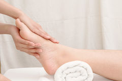Therapist's hands massaging female foot. Foot massage, therapist's hands massaging female foot Royalty Free Stock Image
