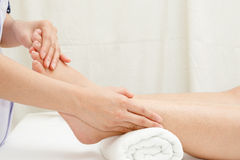 Therapist's hands massaging female foot. Foot massage, therapist's hands massaging female foot Royalty Free Stock Photography
