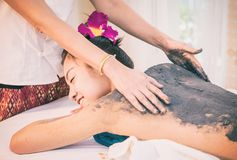 Therapist is scrubbing Charcoal clay scrub cream on a women back Royalty Free Stock Image