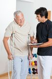 Therapist With Senior Man. Happy therapist writing report while standing with senior men on crutches Royalty Free Stock Photos