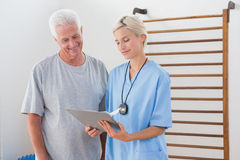 Therapist showing clipboard to senior man. Therapist showing clipboard to senior men in fitness studio Royalty Free Stock Photography