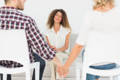 Therapist smiling at reconciled couple holding hands stock images