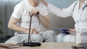 Therapist talking with senior male patient at home, writing down medical records stock images