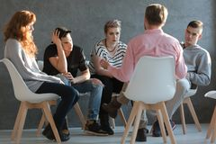 Therapist talking to young rebellious people. With problems Royalty Free Stock Image