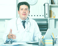 Therapist in uniform filling up documents. Young and smiling therapist in uniform filling up documents Stock Photos