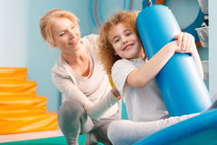 Therapist watching a boy on disc swing. Smiling therapist watching a boy on disc swing during therapy session stock photo