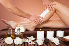 Therapist Waxing Customer's Leg At Beauty Spa. Cropped image of male therapist waxing female customer's leg at beauty spa Stock Images