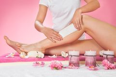Therapist waxing customer's leg at spa. Midsection of female therapist waxing customer's leg at beauty spa Stock Photos