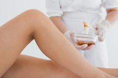 Therapist waxing woman's leg at spa center Stock Photography