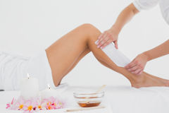 Therapist waxing woman's leg at spa center Royalty Free Stock Photography
