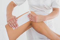 Therapist waxing woman's leg at spa center Royalty Free Stock Images