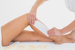 Therapist waxing woman's leg at spa center Stock Photo