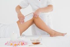 Therapist waxing woman's leg at spa center Stock Photos