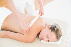 Therapist waxing womans back at spa center Royalty Free Stock Image