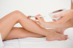 Therapist waxing womans leg at spa center Stock Image