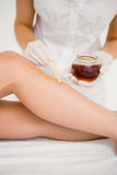 Therapist waxing womans leg at spa center Stock Photography