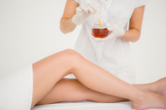 Therapist waxing womans leg at spa center Royalty Free Stock Images