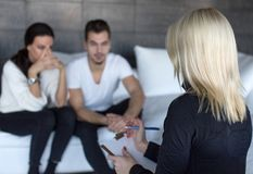 Therapist woman talking with young sad couple royalty free stock photos