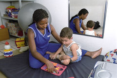 Therapist at work with handicapped child, Brazil. Brazil, Pernambuco, city Gravata: a woman is to stimulate the sense of form, understanding and motor skills of Royalty Free Stock Photos