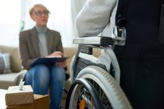 Therapist Working with Handicapped Patient. Portrait of female psychiatrist interviewing handicapped men during therapy session, copy space royalty free stock images