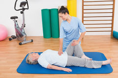 Therapist working with senior woman on exercise mat Stock Photos