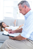 Therapist writing on notepad with female patient Stock Photo