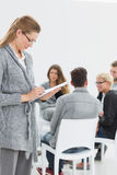Therapist writing notes with group therapy in session Stock Images