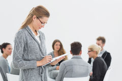 Therapist writing notes with group therapy in session Royalty Free Stock Photography