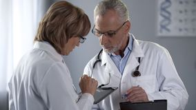 Therapists discussing analysis results, woman holding tablet, man with notepad. Stock photo stock photo