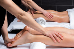 Therapists doing calf massage on couple. Close up of simultaneous leg massage on couple in spa.Two physiotherapists applying pressure on couples legs Royalty Free Stock Images