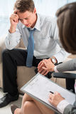 Therapy comforting. Vertical image of a psychiatrist comforting worried patient at session Royalty Free Stock Photos