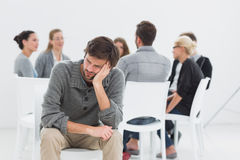 Therapy in session in circle while man in foreground Royalty Free Stock Photo