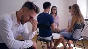 Therapy session, sad man thinks about problems on background of people sitting on chairs in circle stock video footage