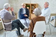 Therapy Session for seniors. Portrait of blonde female psychiatrist leading group therapy session for senior people in retirement home, copy space, copy space stock photos