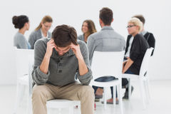 Therapy in session sitting in circle while man in foreground Stock Images