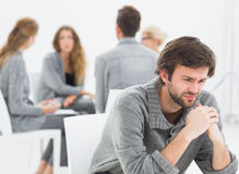 Therapy in session sitting in a circle while man in foreground Royalty Free Stock Photo