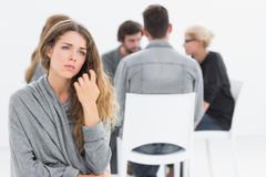 Therapy in session sitting in a circle while woman in foreground Royalty Free Stock Images