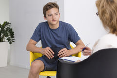 Therapy session with a teenager. Teenage boy in therapy session with female psychologist Stock Photo